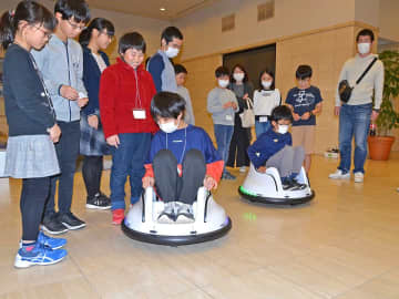 動きを組み込んだプログラムを電動運転車に差し込み、動きを確かめる子どもたち=岐阜新聞本社