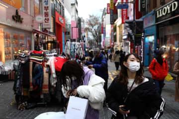新型コロナウイルスの感染者が急増する韓国のソウルで、マスクをして歩く人々=22日(ゲッティ=共同)