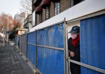 中国・武漢市で、外出が制限されフェンスで囲まれた集合住宅の敷地から外をのぞく男性=21日(共同)