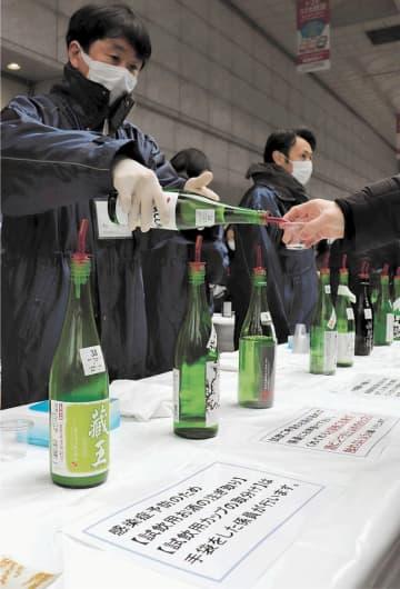 マスクとゴム手袋を着用し、試飲の新酒を提供する宮城の酒蔵関係者ら=22日、仙台市青葉区の藤崎前