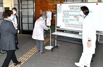 正面玄関で、看護師と事務職員が厚労省が示した「受診の目安」を説明し、手指消毒への協力を呼び掛けている=21日、山形市・県立中央病院