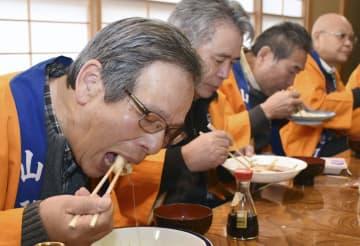餅をかまずにのみ込む「溝延一升宝餅保存会」の会員=23日、山形県河北町
