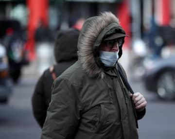 米ニューヨークで新型コロナウイルスの感染を警戒し、マスクをして歩く人=1月30日(ゲッティ=共同)