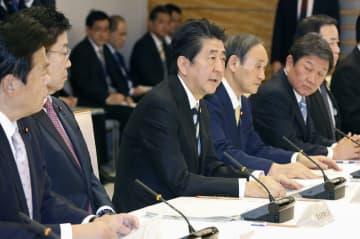 新型コロナウイルス感染症対策本部会合で発言する安倍首相(手前から3人目)=23日午後、首相官邸
