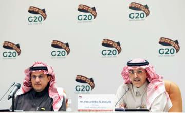 記者会見するサウジアラビアのジャドアーン財務相(右)ら=23日、リヤド(ロイター=共同)