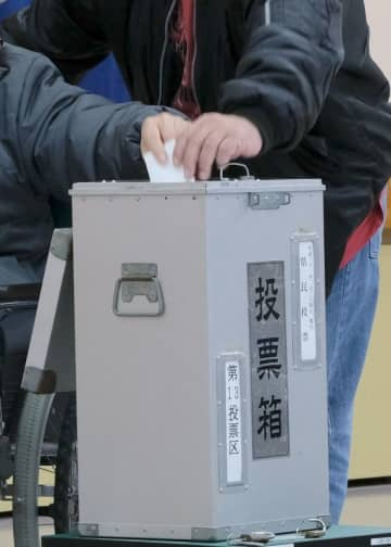 (資料写真)車いすに乗って1票を投じる男性