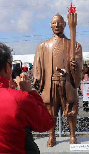 【武四郎まつりでお披露目した聖火トーチを持つ松浦武四郎像=松阪市小野江町で】