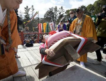 力を込めて巨大な鏡餅を持ち上げる女性参加者(23日午後0時40分、京都市伏見区・醍醐寺)