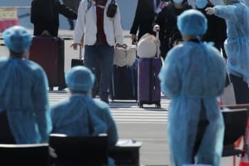 時事通信 クルーズ船「ダイヤモンド・プリンセス」から下船し、大きな荷物を運ぶ乗客とみられる人たち。手前は防護服を着た関係者=2月21日午後、横浜・大黒ふ頭