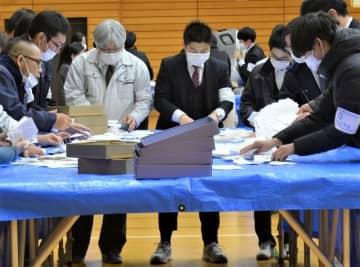 マスク姿で市議選の開票作業を行う市職員ら=23日夜、四街道市