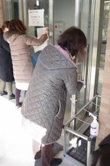 京都大で入試会場の扉を消毒するなど準備を進める職員ら(京都市左京区)