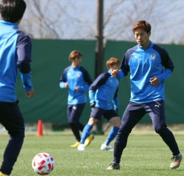 練習する大分のMF佐藤(右)ら=県サッカー協会スポーツ公園