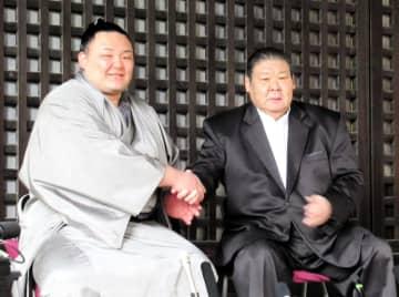 がっちり握手する朝乃山(左)と師匠の高砂親方