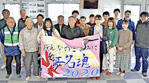 生徒ら手作りの大漁旗を受ける金成さん(前列中央)ら