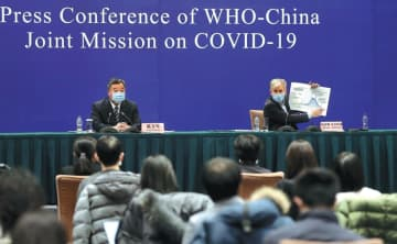 Bruce Aylward, head of the WHO-China Joint Mission on COVID-19's foreign expert panel, holds up a chart showing the results of China's epidemic control efforts at a news conference in Beijing on Monday. WANG ZHUANGFEI / CHINA DAILY