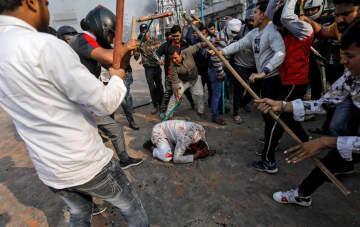24日、インドの首都ニューデリーで、改正国籍法を支持する人々から攻撃されるイスラム教徒の男性(ロイター=共同)