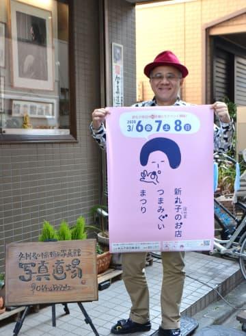 「つまみさん」の描かれたポスターを手にする久門さん=川崎市中原区