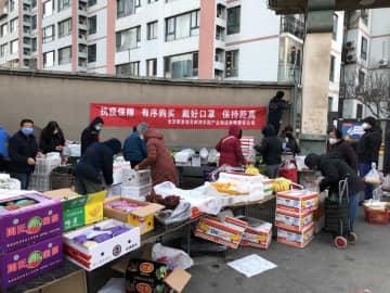 北京市内の団地の前で野菜の行商をする人たち。壁に掲げられたスローガンは「マスクをかけ、人との距離を保とう」(2020年2月24日)