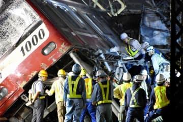 大きく傾いた車両を柱で支えながら大勢の作業員が復旧にあたった=6日午前3時10分ごろ、横浜市神奈川区