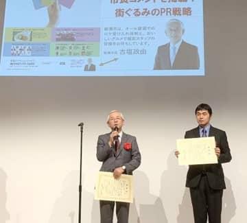 表彰式であいさつする古塩市長(左)=20日、都内(綾瀬市提供)