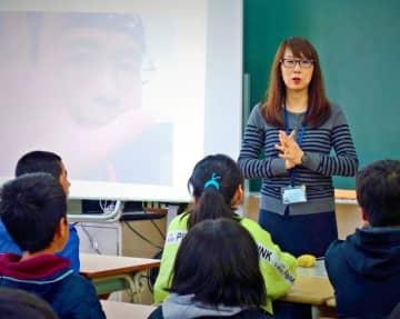 がんになった経験を6年生の児童に伝える野田真記子さん。患者仲間だった故上水流政美さんのスライドも使いながら、命の大切さを訴えた=3日、那覇市立真地小学校
