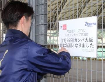 26日のG大阪戦延期を伝える張り紙を設置する大分FCのスタッフ=25日、昭和電工ドーム大分