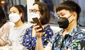 Commuters wearing protective face masks amid fears of the spread of the COVID-19 coronavirus ride an elevated train in Bangkok.