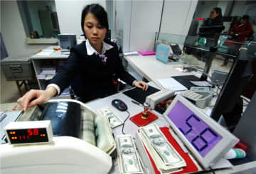 A teller counts foreign currency at a bank in Jiujiang, Jiangxi province.[Photo by Hu Guolin/For China Daily]