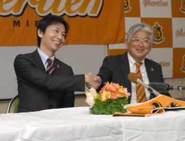 【「Jリーグ百年構想クラブ」認定の連絡を受け、山本好彦GMと握手するヴィアティン三重の後藤大介代表(左)=桑名市の同クラブ事務局で】