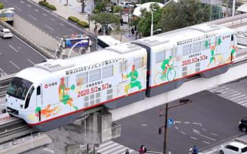 東京五輪聖火リレーのラッピングで走るゆいレールの車両=25日午後、那覇市久茂地(下地広也撮影)