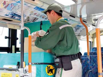 国際興業の路線バスに荷物を積み込むヤマト運輸のドライバー=25日午後、飯能市柳町の国際興業飯能営業所
