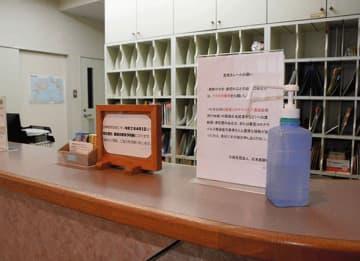 受付にマスク着用などを呼び掛ける掲示物や消毒用アルコールを置いているまえだクリニック=熊本市北区
