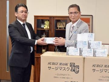 久喜邦康市長(右)にマスクを手渡す落合正雄社長=25日午後、秩父市役所