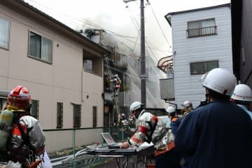 煙を上げて燃える民家に放水する消防隊員ら(26日午前11時59分、京都市上京区栄町)