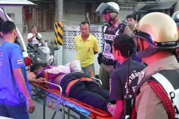 The man shot several times during a gunfight with police in Muang district, Nakhon Si Thammarat, on Wednesday morning is taken to an ambulance before being rushed to a hospital, where he died.  (Photo by Nujaree Raekrun)