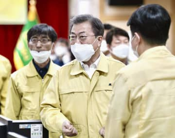 25日、韓国・大邱で開かれた新型コロナウイルスの対策会議に出席する文在寅大統領(中央)(聯合=共同)