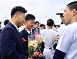 後輩の野球部員から花束を贈られる(左から)重宮涼さん、水上桂さん=明石市魚住町長坂寺