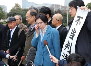 判決を受け「残念です」と涙を拭う内藤さん(中央)=東京、最高裁判所前
