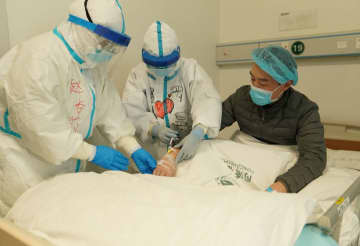 Medical workers inject medicine for Li Zuofan (R) at an intensive care ward of the novel coronavirus infection cases at Tongji Hospital in Wuhan, Central China's Hubei province, Feb 18, 2020. [Photo/Xinhua]