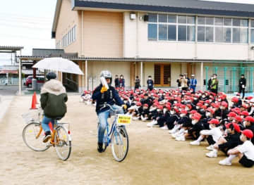児童たちの前で、自転車の危険な運転を実演する両選手