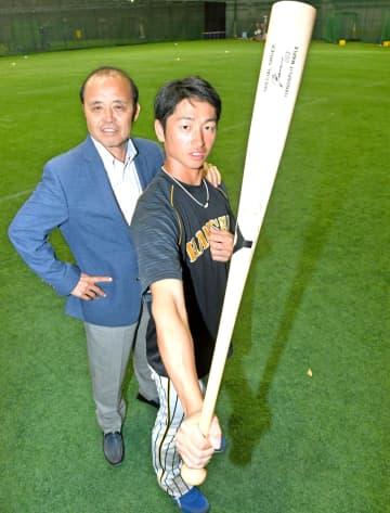 岡田彰布氏(左)からエールを受け、バットを手にポーズを決める近本