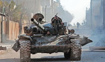 Turkey-backed Syrian fighters ride a tank in the town of Saraqib in the eastern part of the Idlib province in northwestern Syria, as fierce fighting raged on in its outskirts on Thursday.