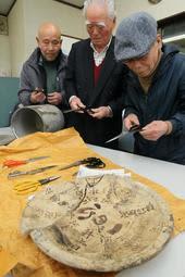 タイムカプセル(奥)に入っていた自作のラシャ切りばさみを手にする(右から)井上隆敏さん、井上日吉さん、河島金次さん=河島製鋏所