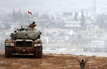 Turkish army tanks manoeuver as Turkish Kurds watch over the Syrian town of Kobani (photo credit: REUTERS)