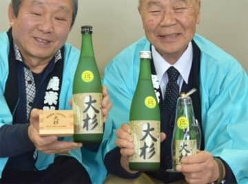 15周年を迎えた「純米吟醸 大杉」を手にするNPO法人のメンバー(京都府舞鶴市北吸・市役所)