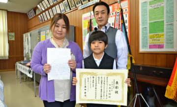 受賞を喜ぶ川満天翔さん(中央)と父誠さん、母優子さん=28日、沖縄市の宮里小学校