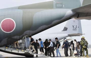 タイ中部のウタパオ海軍航空基地で行われた訓練で、自衛隊員に警護されて輸送機に乗り込む退避者役の邦人ら=29日(共同)