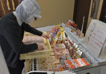 納品予定だった給食用納豆を無料配布用に陳列する販売員=29日午前、水戸市柳町