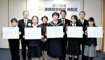 表彰状を受けた(前列右から)橋本さん、猪俣さん、永井さん、広田さん、山口君。(後列右から)佐藤、渡辺両課長、中村会長、中尾常務