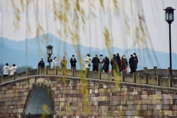 People visit the West Lake scenic area in Zhejiang province's Hangzhou, Feb 19, 2020. Some scenic spots in the country have reopened. Scenic areas limit the number of visitors to prevent the spread of the novel coronavirus. [Photo/Xinhua]
